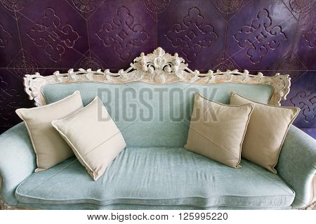 Old fashioned sofa on purple wall, vintage style.