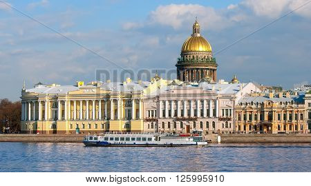 SAINT - PETERSBURG, RUSSIA - APRIL 16, 2016: Tourists in the excursion boat sail on The Neva River along The English Embankment in spring time. On the background is Saint Isaac's Cathedral