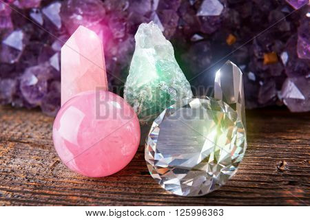 Fluorite also called fluorspar natural crystal, rose quartz, rhinestone and amethyst rock in background