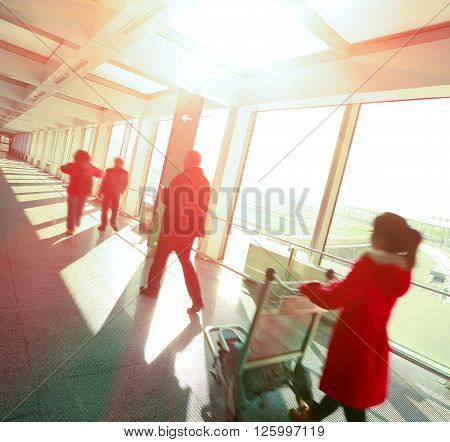 Sunny on passengers in modern airport interior glass wall aisle windows of people