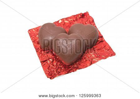 Three chocolate heart candy in red foil on white background, chocolate candy concept , chocolate candy idea, chocolate candy background, chocolate candy isolated, chocolate candy valentine.