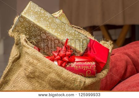 Christmas presents stacked to the brim inside a brown hessian bag resting near some red pillows inside a home.