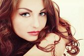 Vintage style portrait of young beautiful woman with eyebrows tattoo and long curly hair poster