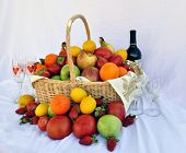 foto of tangelo  - A Basket of assorted fruit with a wine bottle and wine glasses with a white cloth background - JPG