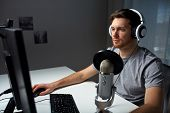 technology, gaming, entertainment, lets play and people concept - young man in headset with pc comp poster