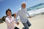 stock photo of 55-60 years old  - Portrait of a senior couple running on the beach - JPG