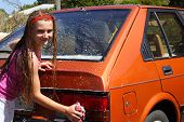 picture of car wash  - cute girl washing tail light on car - JPG