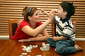 picture of babysitter  - child and teen playing with dominos at kitchen table - JPG