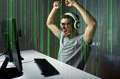 technology, gaming, entertainment, lets play and people concept - happy young man in eyeglasses wit poster