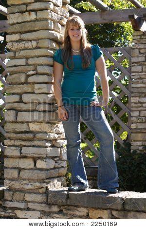 Teenage Girl Standing On A Brick Wall