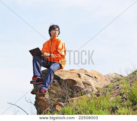 man using computer on the rock outdoor