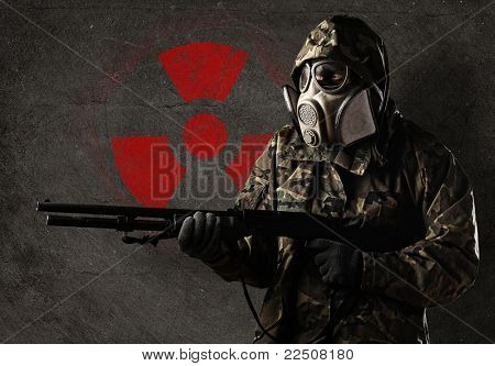armed soldier wearing a gas mask against a concrete wall with red radioactive symbol