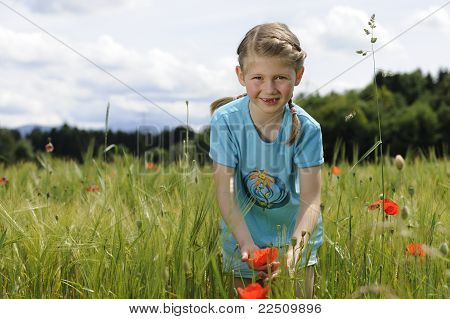 Cute girl in poppy flower field