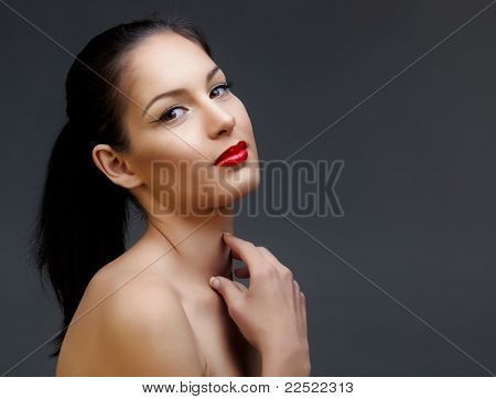 beautiful woman with long black hair in ponytail and shiny skin wearing classic red lipstick and beautiful skin texture