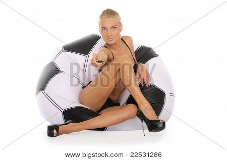 Woman with remote control in chair in the form of soccer ball