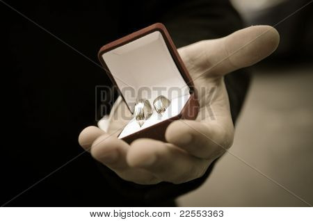 wedding rings in groom's hands