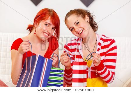 Two Smiling Girlfriends With Shopping Bags