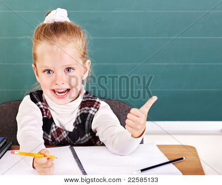 Happy schoolchild in classroom near blackboard.
