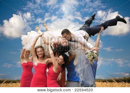 A happy groom and bride  tossed into sky by a group of friends