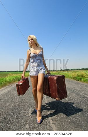 Pretty woman walking on the road with her baggage