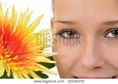 Close-up of a woman with a yellow-red flower