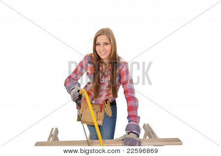Young woman sawing a board