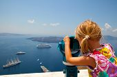 stock photo of cruise ship  - Girl looking at cruise ships with binoculars in Thira Santorini Greece - JPG