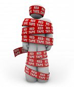 A person is wrapped up in red ribbon with the words Red Tape repeated, representing getting caught u