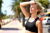 Runner girl tired feeling exhausted from jogging outside in summer heat -sun stroke headache or dehy poster