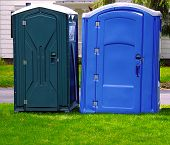 picture of porta-potties  - Two portable bathrooms on a cloudy overcast day - JPG