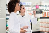 Side view of two dedicated female pharmacists looking for the best medicine in the stock while worki poster