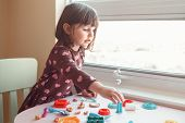 Portrait Of Cute White Caucasian Preschooler Girl Playing Plasticine Playdough Indoors At Home. Earl poster