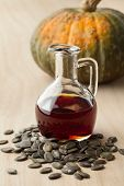 Bottle with tasty pumpkin seed oil and roasted seeds  poster