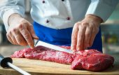 Hands of male chef in uniform cutting big piece of beef on board in restaurant kitchen. Man cuts mea poster