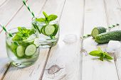 Summer Refreshing Detox Cocktail. Water With Cucumber, Mint And Ice In Glass On A White Wooden Backg poster