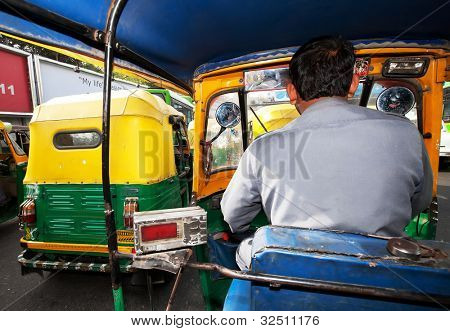 NEW DELHI, INDIA - MARCH 09 : Auto rickshaw taxis on a road on March 09, 2012 in Delhi, India. These iconic taxis have recently been fitted with CNG powered engines in an effort to reduce pollution
