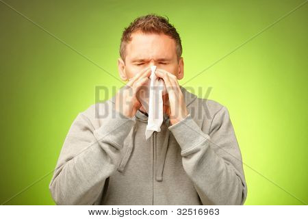 Man having a cold holding tissue and blowing his nose
