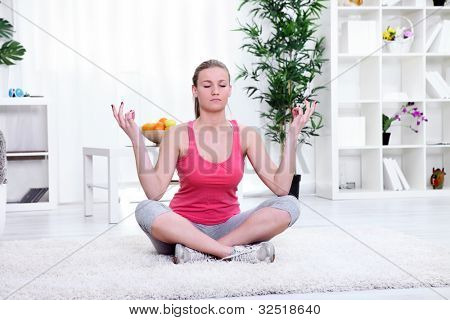 Relaxed woman sitting and meditating at home