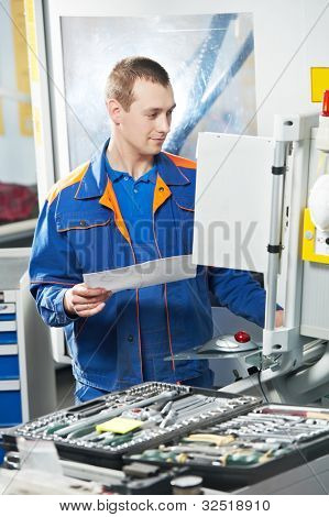 mechanical technician laborer working on modern cnc metal machining milling center in tool manufacturing workshop