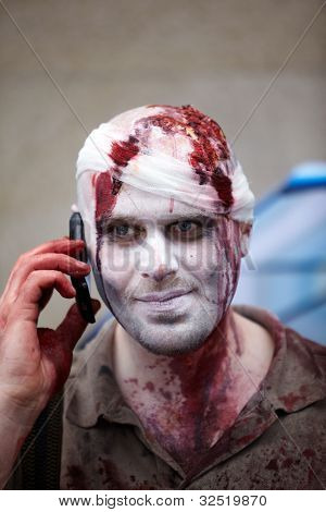 MOSCOW - MAY 14: Unidentified made-up participant with a bandaged bloody head keeps cell phone at his ear at Zombie Parade on Old Arbat, May 14, 2011, Moscow, Russia.