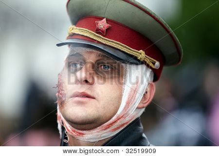 MOSCOW - MAY 14: Unidentified participant in the soviet-style military cap with wounded face and bandaged head at Zombie Parade on Old Arbat, May 14, 2011, Moscow, Russia.