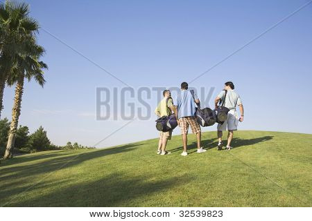 Three men walking on golf course
