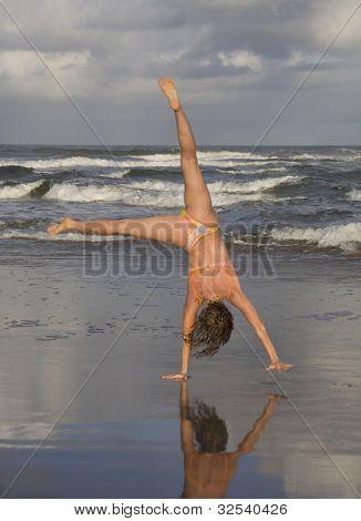 Woman doing cartwheel on beach