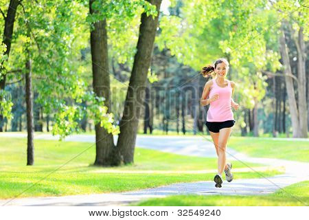 Jogging woman running in park in sunshine on beautiful summer day. Sport fitness model of mixed Asian / Caucasian ethnicity training outdoor for marathon.