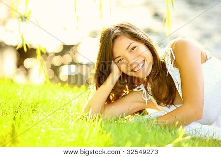 Summer girl in grass smiling happy. Lifestyle image of beautiful young woman in summer dress lying joyful in park on sunny sunshine day. Mixed race Caucasian / Asian Chinese female model.