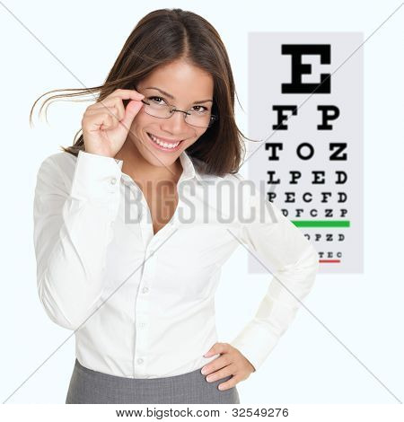 Optician or optometrist showing Snellen eye exam chart wearing eye wear glasses. Female mixed race Caucasian / Asian Chinese model