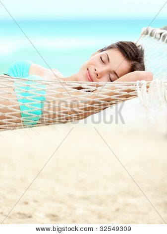 Vacation woman relaxing on beach in hammock on summer holidays resort. Beautiful happy multiracial Asian Chinese / Caucasian young woman.