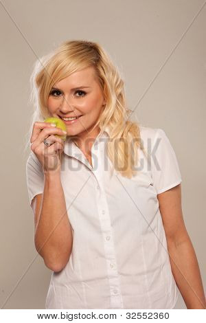 Smiling casual blonde woman eating a green apple on a white studio background