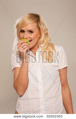 Smiling blonde woman in white shirt eating green apple