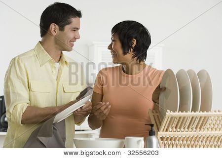 Hispanic couple drying dishes
